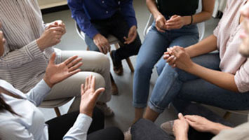 People sitting in a circle discussing evidence based treatment