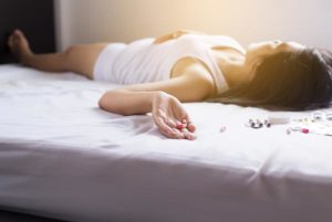 Woman on her bed suffering from a potential vicodin overdose