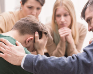 Man being comforted by family members